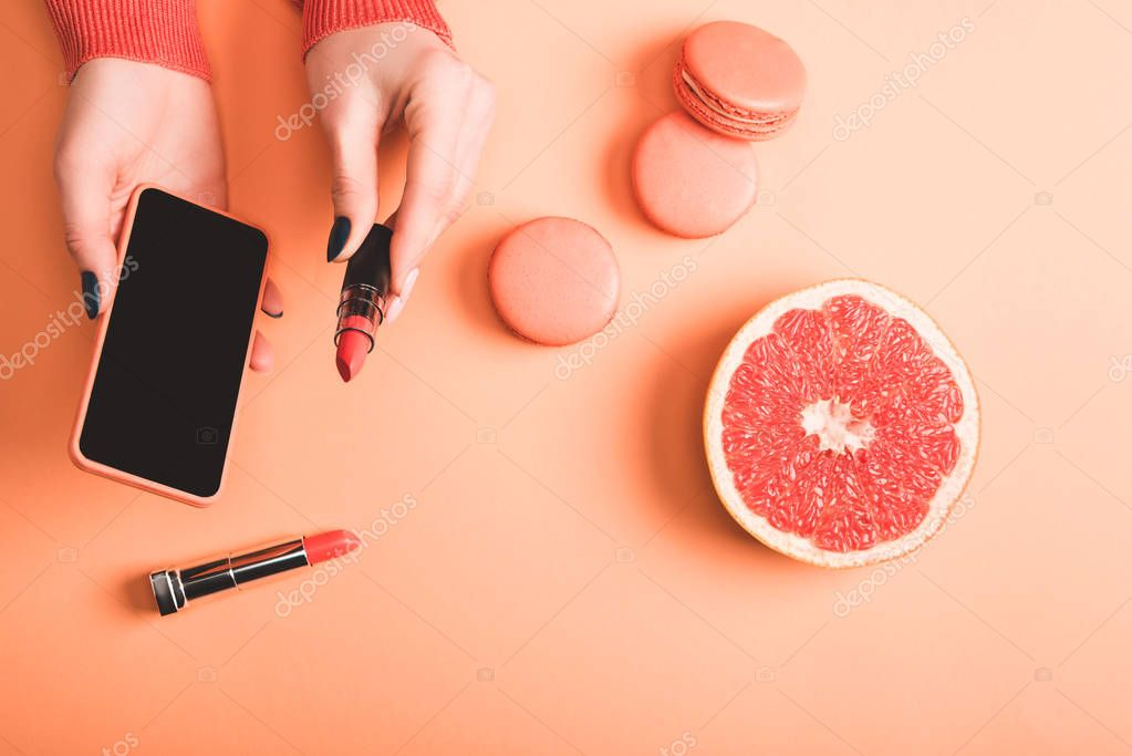 Cropped view of woman holding smartphone and coral lipstick, macarons and grapefruit half on coral background, color of 2019 concept