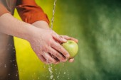Fotografie partial view of man washing apple under blowing water on blurred background, earth day concept
