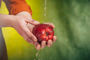 selective focus of man washing apple under blowing water on blurred background, earth day concept