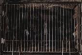 pohled shora tmavě černé přírodní uhlí pod grilovací mřížky železa