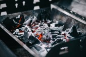 selective focus of hot burning coals with ash in iron bbq grill