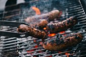 selective focus of tweezers with grilled sausage on barbecue