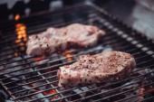 Fotografie Selektivní fokus šťavnaté syrové steaky grilování grilovací mřížky
