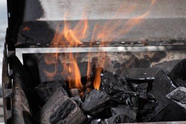 bright burning black coals in iron barbecue grill