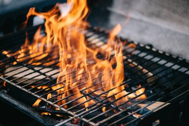 burning firewood with flame through bbq grill grates