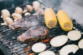 Fotografie selective focus of juicy tasty steaks grilling on bbq grid with mushrooms, corn and sliced eggplant