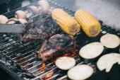 szelektív összpontosít, csipesz, és a szaftos, ízletes steak grill rács, gomba, kukorica, szeletelt padlizsán grillezés