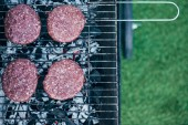 top view of fresh burger cutlets grilling on bbq grid