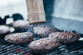 Selektivní fokus soli pádu z solný mlýn na chutné grilované bbq burger kotlety