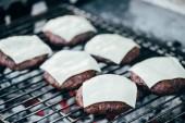 Selektivní fokus kotlety grilované čerstvé burger se sýrem na grilovací mřížky