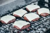 Fotografie Selektivní fokus čerstvé burger kotlety se sýrem grilování grilovací mřížky