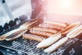 delicious hot dogs grilling with smoke on barbecue grill grade