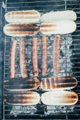 top view of tasty hot dogs grilling with smoke on bbq grill grade