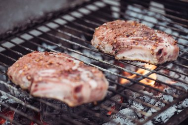 selective focus of juicy raw steaks grilling on barbecue grid