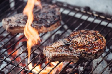 Selective focus of juicy tasty steaks grilling on barbecue grill grade with flame stock vector