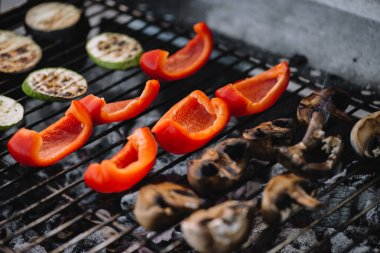 Selective focus of red bell pepper, zucchini and mushrooms grilling on barbecue grill grade stock vector