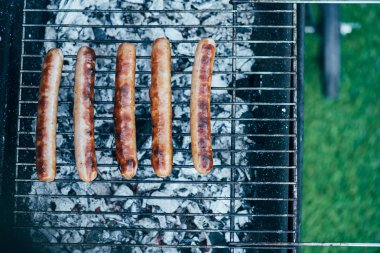 top view of tasty grilled sausages on bbq grill grade on green grass background