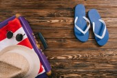 top view of summer accessories and flip flops near suitcase on wooden background