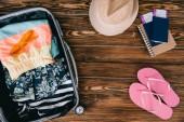 Fotografie pohled shora pasů s lístky a letní oblečení v cestovní tašce na dřevěný povrch