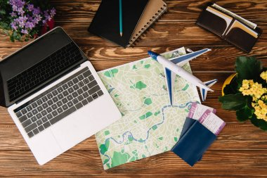 Top view of laptop, map, passports with tickets and plane model on wooden surface stock vector