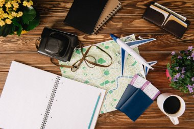 top view of film camera, coffee cup, empty notebook, map, passports with tickets and plane model on wooden surface