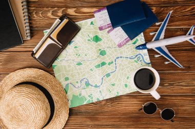 top view of accessories, map, passports with tickets and plane model on wooden surface