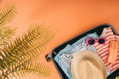 Fotografie top view of suitcase with summer accessories and sunscreen on orange background with palm leaves