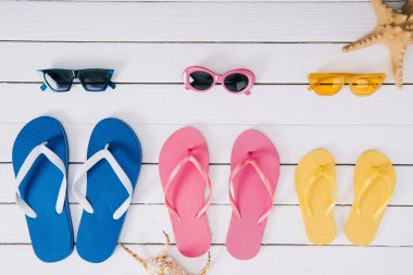 Set of yellow, blue and pink sunglasses and flip flops on white wooden background stock vector