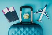 horní pohled na zeměkouli a letadlo modelů, cestovní tašky a pasy s lístky na modrém pozadí