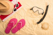top view of summer accessories and swimming mask with snorkel on sand