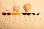 top view of sunglasses and seashells with smiles drawn on sand