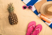 top view of summer accessories, sunscreen on striped towel and pineapple on sand