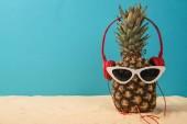 ananász a fejhallgató és a napszemüveg, a homok, kék alapon