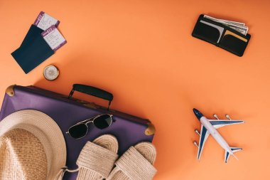 top view of summer accessories on travel bag, plane model, wallet and passports with tickets on orange background