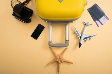 Top view of yellow suitcase, plane model, starfish, film camera, smartphone and tickets on beige background stock vector
