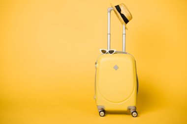 bright yellow suitcase, sunglasses and straw hat on yellow background