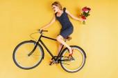 Hezká mladá žena s kytice, jízda na kole na žlutém podkladu