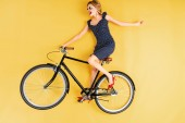 Joyful woman in sunglasses and dress riding on bicycle on yellow background