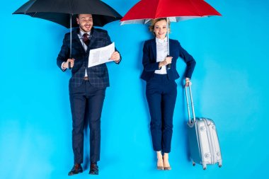 Woman with valise and man with newspaper standing under umbrellas on blue background