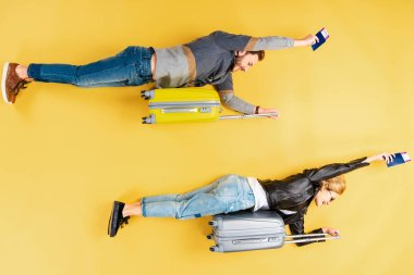 Funny couple lying on suitcases and holding tickets on yellow background