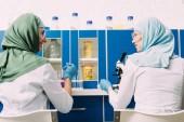 zadní pohled na ženské muslimské vědce pomocí pipety a mikroskop v chemické laboratoři