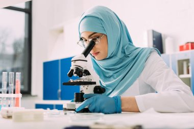 concentrated female muslim scientist looking through microscope during experiment in chemical laboratory