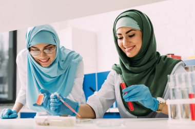 Smiling female muslim scientists in hijab with test tube and pipette during experiment in chemical lab stock vector
