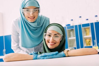 Happy muslim chemists in protective goggles and hijab looking at camera in laboratory stock vector