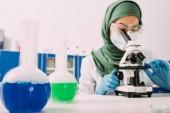 Muslimische Wissenschaftlerin sitzt mit Fläschchen am Tisch und benutzt Mikroskop bei Experimenten im Chemielabor