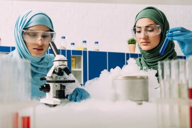 female muslim scientists experimenting with microscope, test tube and dry ice in chemical laboratory