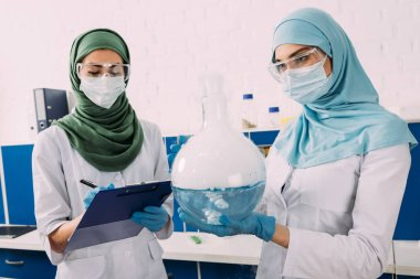 concentrated female muslim scientists in medical masks holding clipboard and flask wth liquid in chemical laboratory