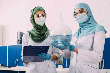 female muslim scientists holding clipboard and flask wth liquid in chemical laboratory
