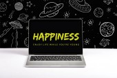 laptop on table with enjoy life while you are young and happiness lettering on screen with white galaxy illustration on black
