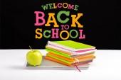 zavření notebooku, zelené jablko, poznámkové bloky a barvu tužky na stole s Vítejte zpět do školy, nápis na černém pozadí